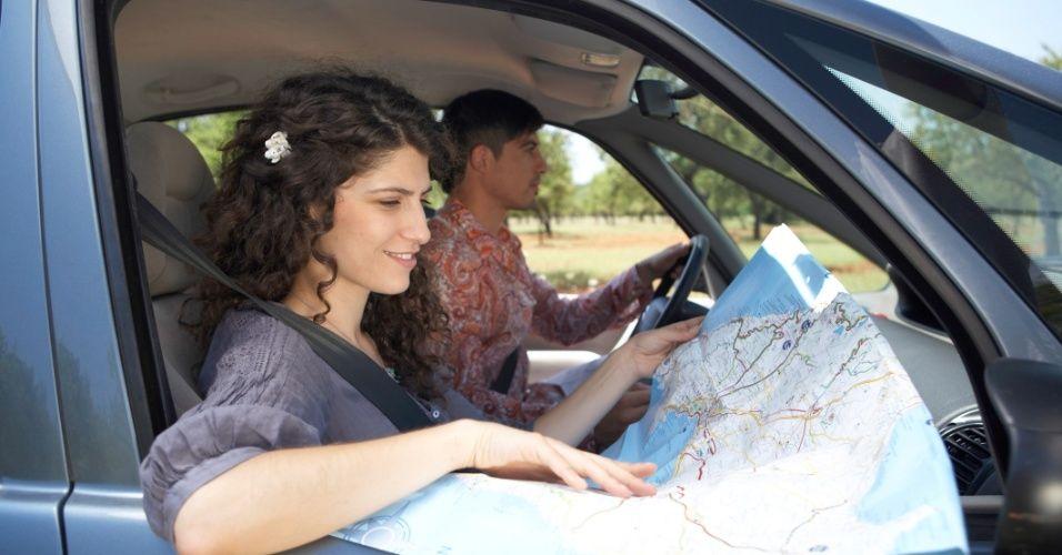 Muher e marido andando de carro e olhando mapa de papel